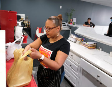 Johanny Cepeda-Freytiz bags up food that was ordered ahead of time for pick up on April 3, 2020, at Mi Casa Su Casa cafe in Reading, Pennsylvania. (Matt Smith for Keystone Crossroads)