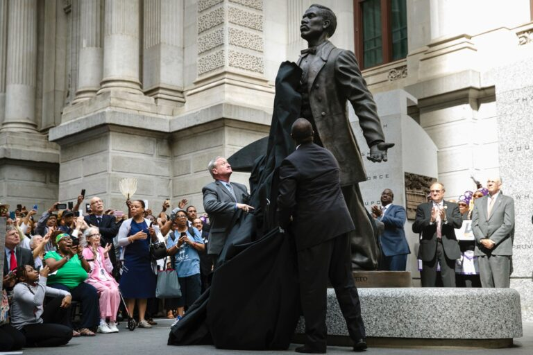 Philadelphia Mayor Jim Kenney (center) and sculptor Branly Cadet unveil a statue of Octavius Valentine Catto at City Hall in Philadelphia, Tuesday, Sept. 26, 2017. A century before the fight to end Jim Crow segregation laws, Octavius Valentine Catto was leading a civil rights movement in Philadelphia. (AP Photo/Matt Rourke)