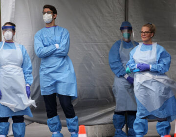 Medical workers wait for cars to pull up to the swabbing tent at the city's coronavirus testing site next to Citizens Bank Park in South Philadelphia on Friday, March 20, 2020. (Tim Tai/The Philadelphia Inquirer via Pool)