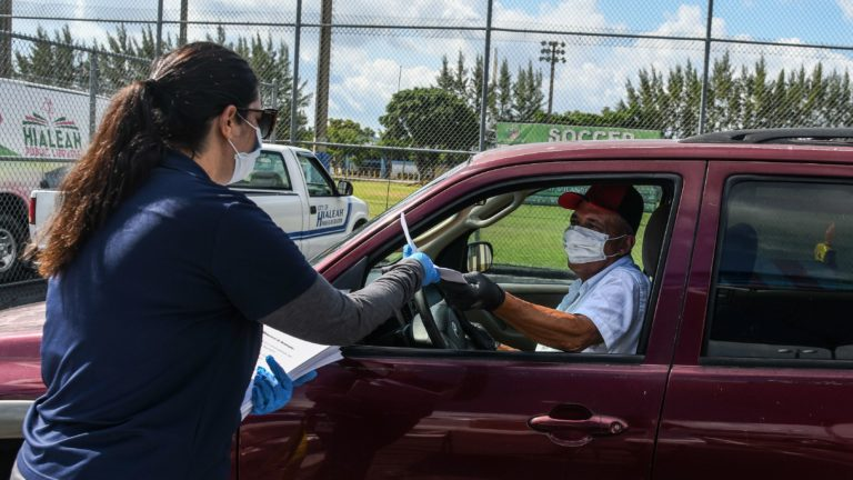A man collects unemployment forms at a drive-through collection point outside of a library in Hialeah, Fla., on Wednesday. (Chandan Khanna/AFP via Getty Images)