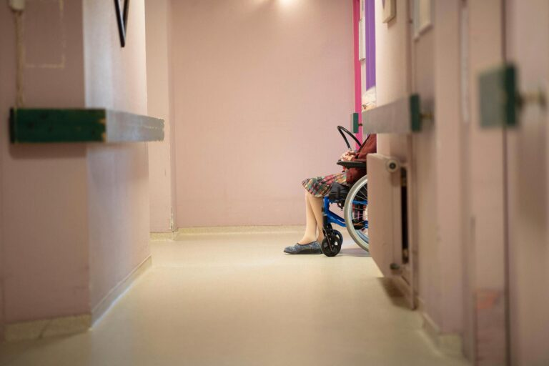A resident is pictured using a wheelchair inside a nursing home.