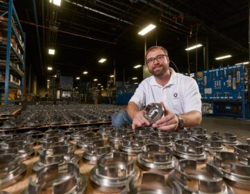 Plant manager Joe Glass poses with automotive parts manufactured by Catalus Corp. (Photo provided by Dave Parsons)