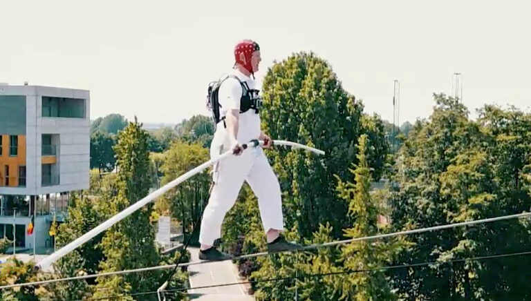 A tight rope walker performs wearing an EEG brain electricity monitor. (Image courtesy of Guy Cheron)