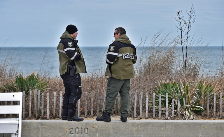 Rehoboth Beach Police patrolmen stand on a wall at an empty boardwalk
