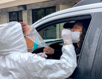 A Black doctor performs a free COVID-19 test in the parking lot of the West Philadelphia Seventh-day Adventist Church. (Christopher Norris for WHYY)