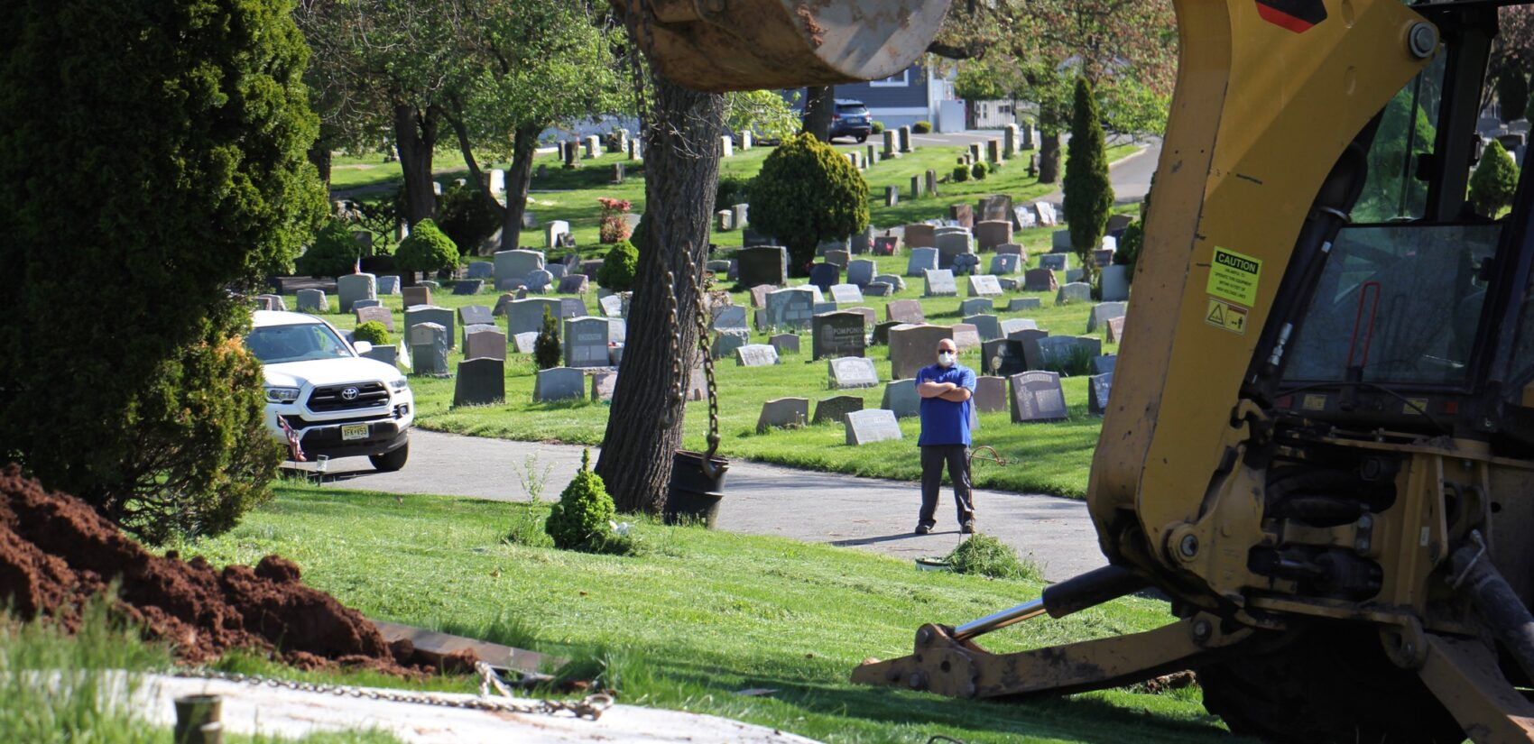 Jeff Dodgson, who oversees the grounds crew at Glendale Cemetery in Bloomfield, N.J., watches as a grave is prepared. (Emma Lee/WHYY)