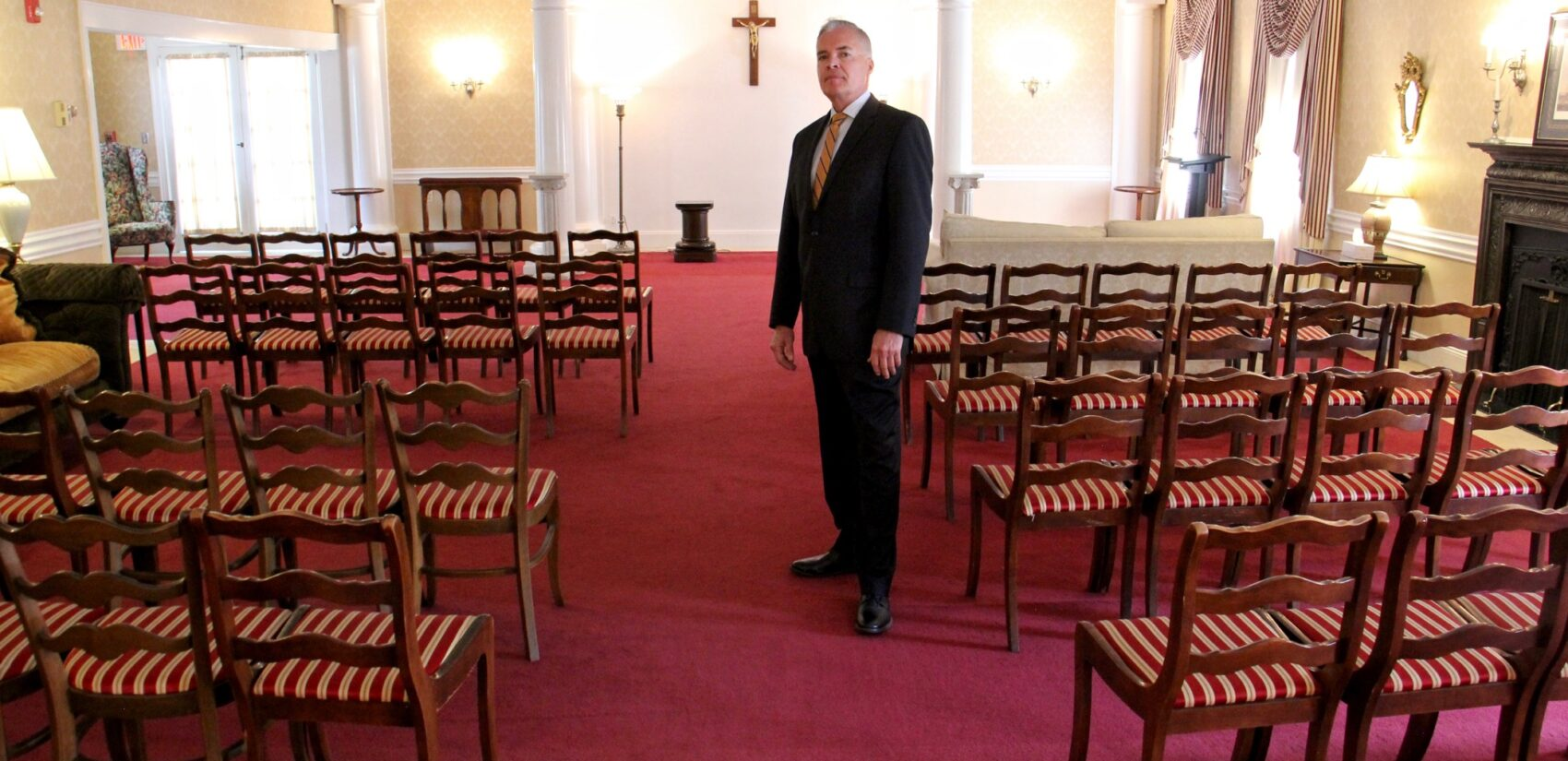 Funeral director Kurt Larsen stands in the empty chapel at Volk Leber Funeral Home in Teaneck, N.J. The chapel hasn't been used since limits on social gatherings went into effect for the region. (Emma Lee/WHYY)