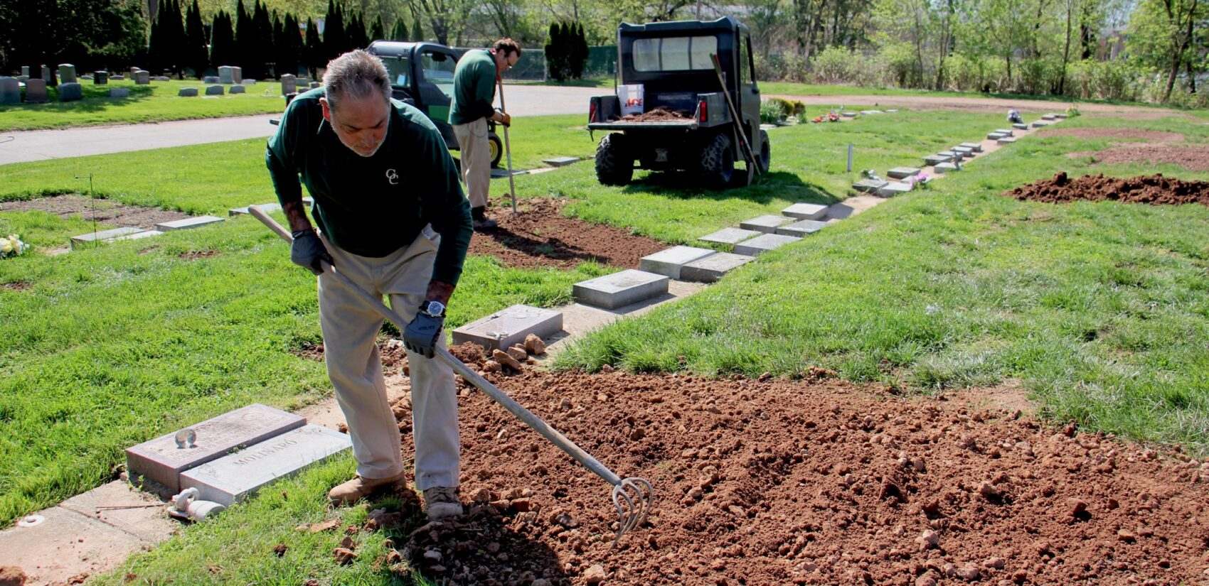 Cemetery workers Pete Sparaco (left) and Frank Mangua tend to fresh graves at Glendale Cemetery in Bloomfield, N.J. 'It's like a war zone,' Sparaco said of the many recent burials. (Emma Lee/WHYY)
