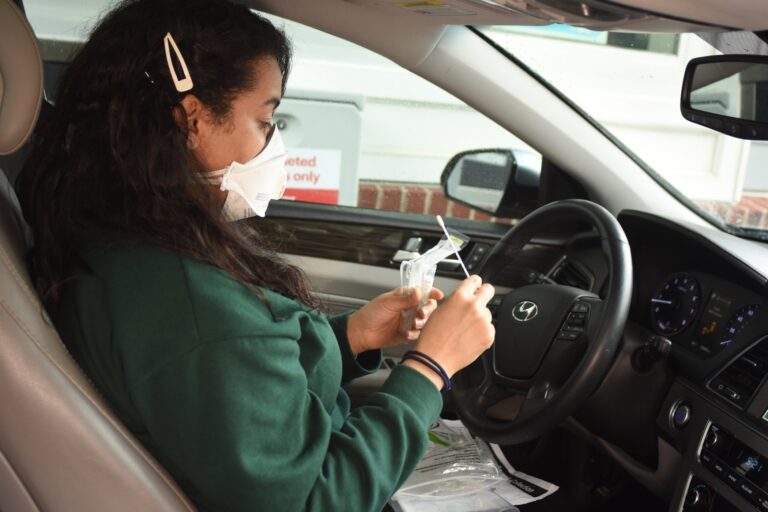 A driver opens a self-testing kit at a CVS drive-through. (Provided by CVS Health)