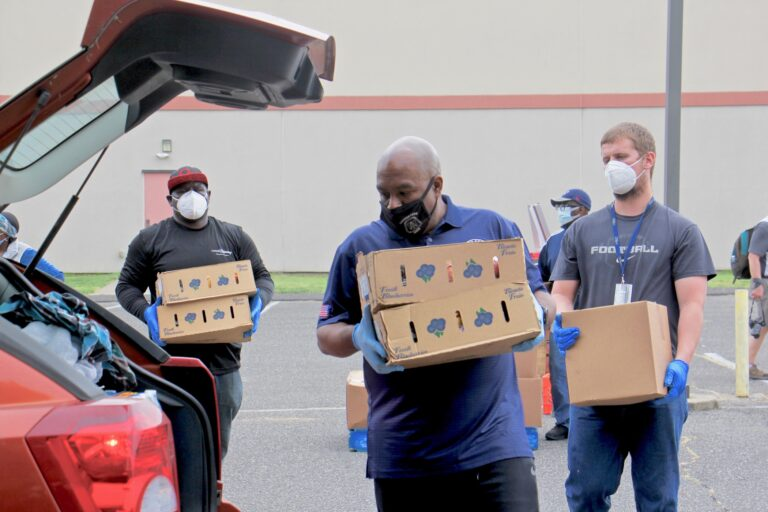 Camden County Freeholder Jon Young (center) and other volunteers and county employees carry boxes of fresh fruit and milk to a waiting car at Antioch Baptist Church.  (Emma Lee/WHYY)