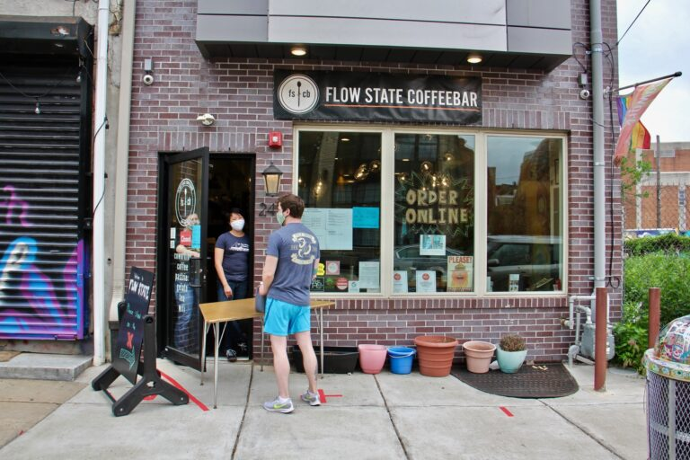 A customer picks up jugs of coffee at Flow State Coffeebar in Fishtown. (Emma Lee/WHYY)