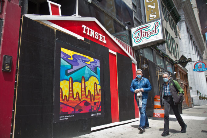 The Mural Arts Program installed works on storefronts boarded up due to coronavirus lockdowns in Center City. This abstract piece on 12th Street is by artist Darin Roland. (Kimberly Paynter/WHYY)