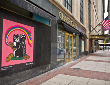 The Mural Arts Program installed works on storefronts boarded up due to coronavirus lockdowns in Center City. This cheerful squirrel across from City Hall is by artist Gina Triplett. (Kimberly Paynter/WHYY)