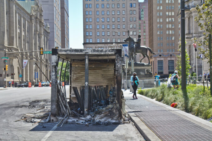 Volunteers pick up trash and debris around a burnt out storage container near City Hall in Philadelphia. (Kimberly Paynter/WHYY)