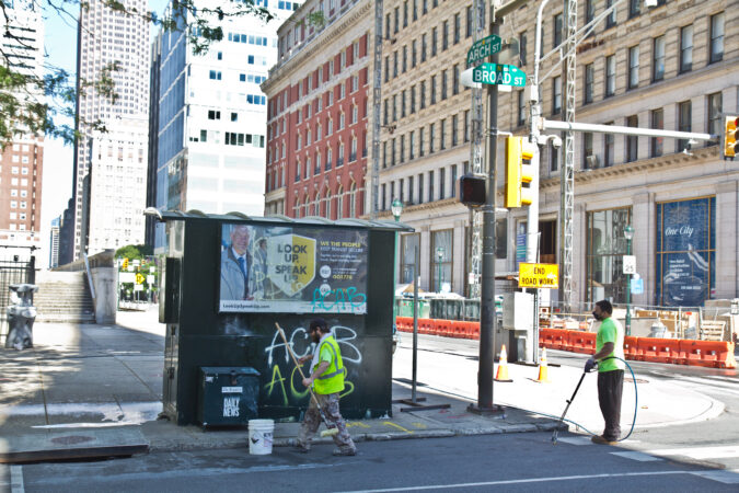 Clip workers scrub graffiti off a newsstand at Broad and Arch Streets in Philadelphia. (Kimberly Paynter/WHYY)