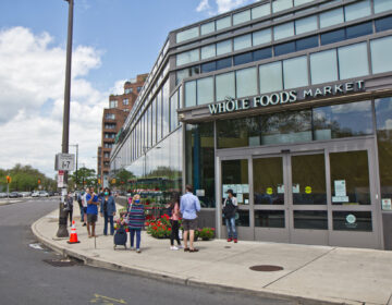 An employee directs people into the store at the Whole Foods grocery in Philadelphia's Fairmount neighborhood. (Kimberly Paynter/WHYY)