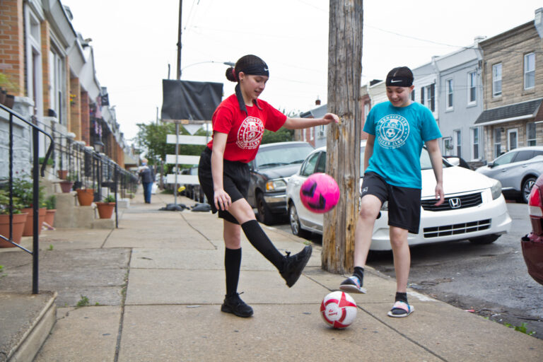 Yvanna, 13, (right), and Emilia, 12, (left) play with soccer balls on their block. (Kimberly Paynter/WHYY)