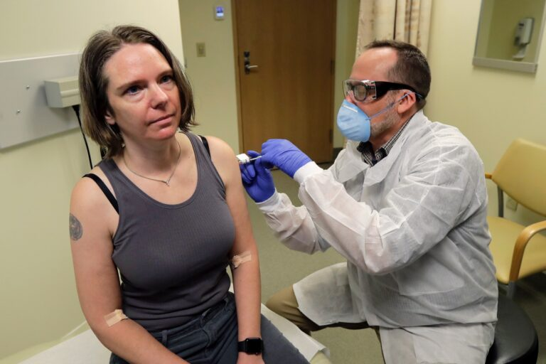 Jennifer Haller (left) is given the first shot in the first-stage safety study clinical trial of a potential vaccine for the COVID-19 coronavirus by a pharmacist, Monday, March 16, 2020, at the Kaiser Permanente Washington Health Research Institute in Seattle. (AP Photo/Ted S. Warren)