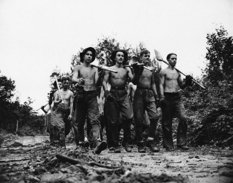 A crew of the Civilian Conservation Camps, which was started in 1933, has taken young men off the bread lines during the depression and put thousands to work.  These men, seen in 1940, were at the CCC's Camp Tomahawk in Wisconsin,. They helped fight forest fires by building fire lanes, clearing brush and the lake.  (AP Photo)