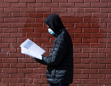 In this Thursday, March 26, 2020, photo, Terrell Bell, wearing a protective face mask, looks at a learning guide he picked up for his little sister at John H. Webster Elementary School in Philadelphia. (AP Photo/Matt Rourke)