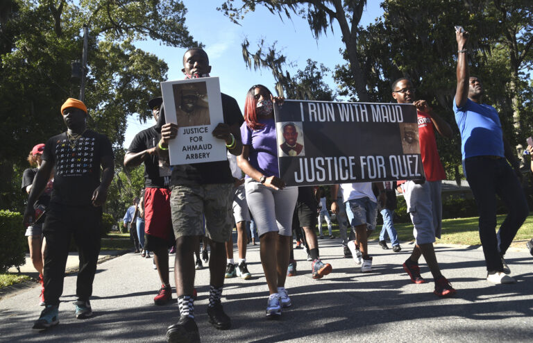 In this Tuesday, May 5, 2020, photo, a crowd marches through a neighborhood in Brunswick, Ga. They were demanding answers in the death of Ahmaud Arbery. (Bobby Haven/The Brunswick News via AP)