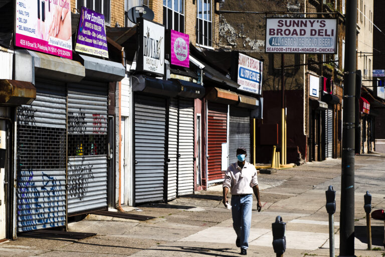 A person wearing a protective face mask as a precaution against the coronavirus walks past stuttered businesses in Philadelphia. (AP Photo/Matt Rourke)