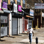 A person wearing a protective face mask as a precaution against the coronavirus walks past stuttered businesses in Philadelphia, Thursday, May 7, 2020. (AP Photo/Matt Rourke)