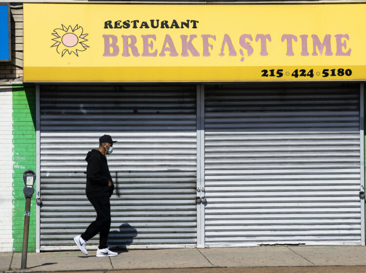 A person wearing a protective face mask as a precaution against the coronavirus walks past a shuttered business in Philadelphia, Thursday, May 7, 2020. (AP Photo/Matt Rourke)