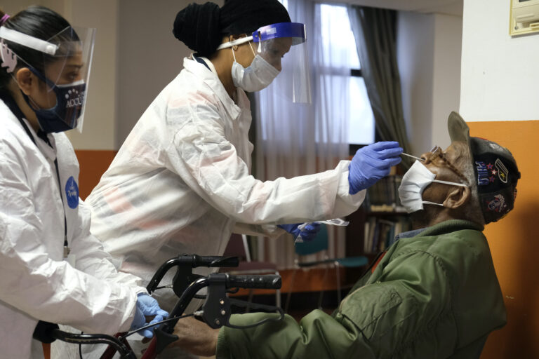 Willie Johnson, right, a resident of senior housing, gets tested for COVID-19 in Paterson, N.J., Friday, May 8, 2020. (AP Photo/Seth Wenig)