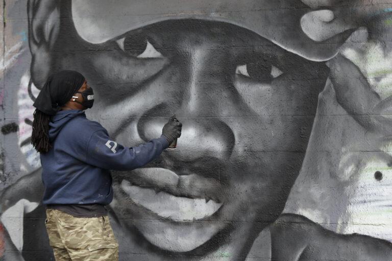 Artist Theo Ponchaveli paints a mural of the likeness of Ahmaud Arbery in Dallas, Friday, May 8, 2020. (AP Photo/Tony Gutierrez)