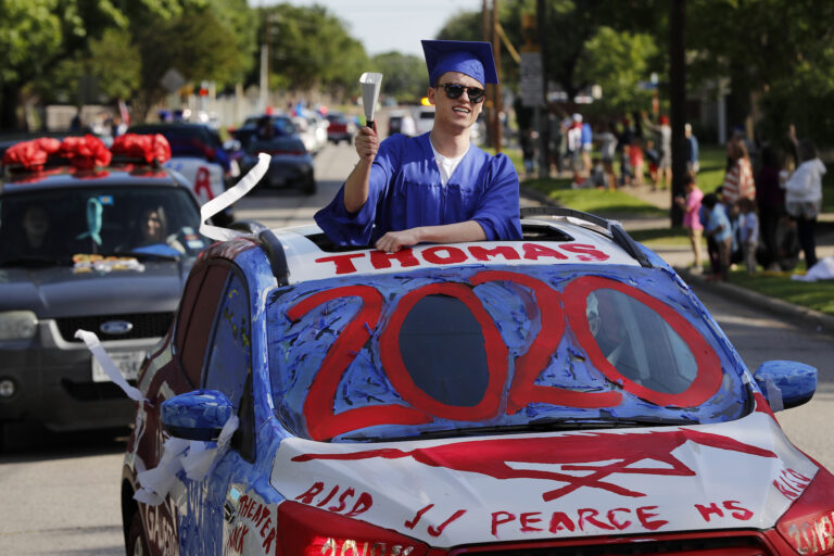 Thomas Harden rings a cowbell as he stands up through the vehicles sun roof waving a supporters during a neighborhood parade honoring 2020 student graduates from both J.J. Pearce and Richardson High Schools in Richardson, Texas, Saturday, May 9, 2020.  (AP Photo/Tony Gutierrez)