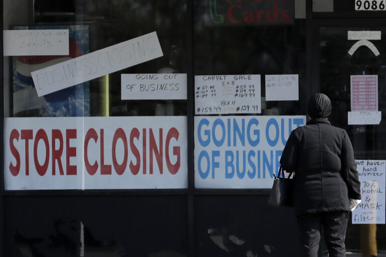 A woman looks at signs at a store closed due to COVID-19. (AP Photo/Nam Y. Huh)