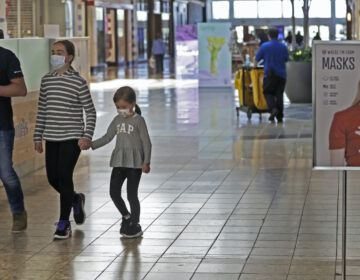 Shoppers walks past a sign encouraging masks at SouthPark Mall, Wednesday, May 13, 2020, in Strongsville, Ohio. (AP Photo/Tony Dejak)