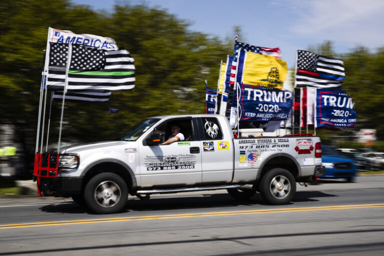 A man drives a truck decorated with flags ahead of President Donald Trump's scheduled visit at Owens and Minor warehouse in Allentown, Pa., Thursday, May 14, 2020. (AP Photo/Matt Rourke)