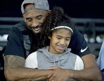Kobe Bryant and his daughter Gianna watch during the U.S. national championships swimming meet