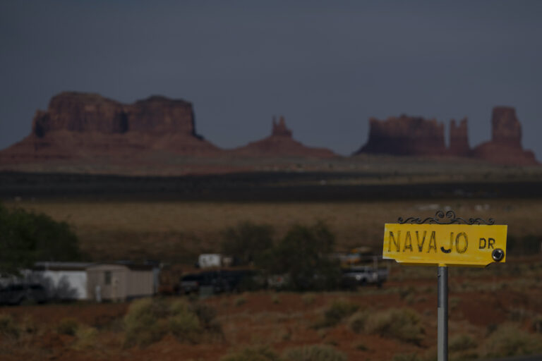 In this April 30, 2020, photo, a sign marks Navajo Drive as Sentinel Mesa, homes and other structures in Oljato-Monument Valley, Utah on the Navajo Reservation, stand in the distance. (AP Photo/Carolyn Kaster)