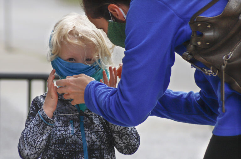 Bridget Kreider, right, helps her three-year-old daughter Maggie pull on her protective face covering before entering a store, Wednesday, May 20, 2020, in Harmony, Pa. Customers entering stores are required to wear face coverings to help prevent the spread of the new coronavirus during the COVID-19 pandemic under the state yellow phase reopening guide. (AP Photo/Keith Srakocic)