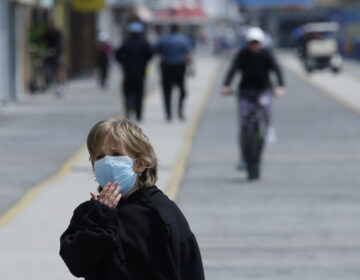 A boy adjusts his mask as he walks down the boardwalk, Thursday, May 21, 2020 in Wildwood, N.J. (AP Photo/Matt Slocum)