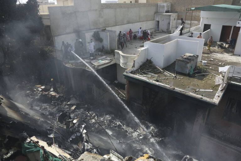 Fire brigade staff try to put out fire caused by plane crash in Karachi, Pakistan, Friday, May 22, 2020. (AP Photo/Fareed Khan)