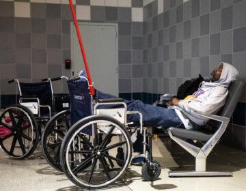 A homeless person sleeps at Philadelphia International Airport in Philadelphia, Monday, May 25, 2020. (AP Photo/Matt Rourke)