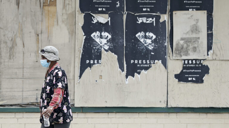 A woman walks past a boarded up business, Thursday, May 28, 2020, in East Cleveland, Ohio. (AP Photo/Tony Dejak)