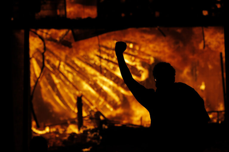 A protester gestures in front of the burning 3rd Precinct building of the Minneapolis Police Department on Thursday, May 28, 2020, in Minneapolis. (AP Photo/Julio Cortez)