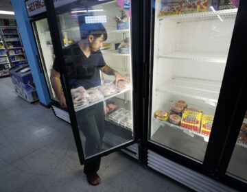 Hardik Kalra stocks meat in a cooler at a local super market, Friday, May 29, 2020, in Des Moines, Iowa. (AP Photo/Charlie Neibergall)