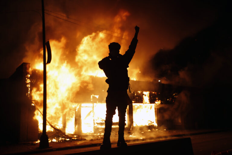 In this May 29, 2020, photo, a check-cashing business burns during protests in Minneapolis. (AP Photo/John Minchillo)