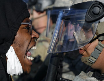 Protesters and National Guardsmen face off on East Lake Street, Friday, May 29, 2020, in St. Paul, Minn. (AP Photo/John Minchillo)