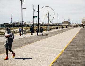 Person wears mask while walking Atlantic City boardwalk