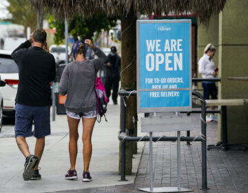 Customers walk past an open sign at Rubio's Coastal Grill