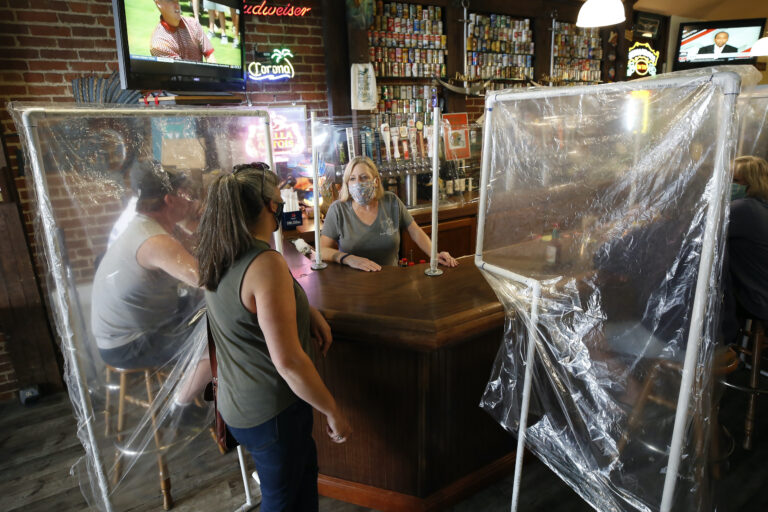 Sheila Kelly stands behind makeshift barriers as she helps patrons at her restaurant