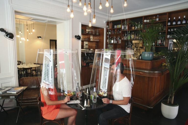 A man and a woman demonstrate dining under a plastic shield amid coronavirus pandemic