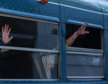 Guatemalans deported from the U.S., wave from a bus.